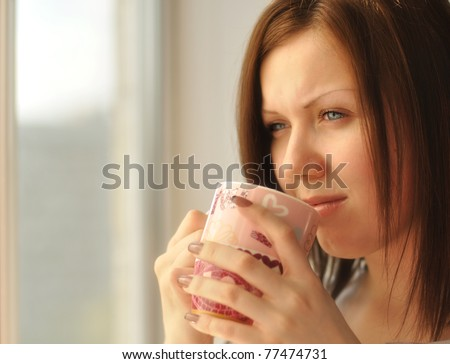 Beautiful sad girl drinking tea and looking out the window, soft focus - stock photo