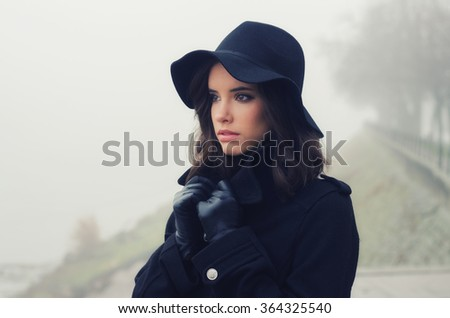 Beautiful sad girl in black clothes, black hat and leather gloves outdoor on moody winter day. - stock photo