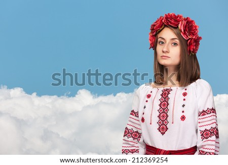 Beautiful sad girl in the Ukrainian national suit against the blue sky with white clouds - stock photo