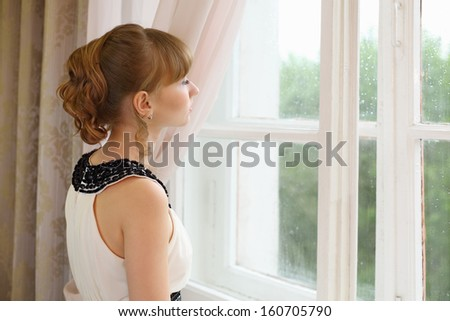 Sad girl in white dress looks in window in light room stock photo