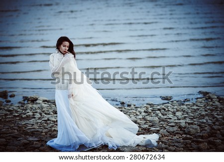 Beautiful sad girl in white dress standing on the sea shore - stock photo