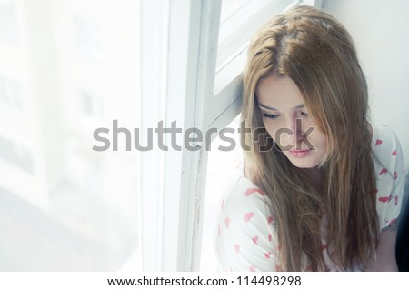 Beautiful sad girl misses the window - stock photo