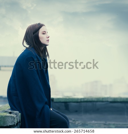 beautiful sad girl on a cloudy day on the roof