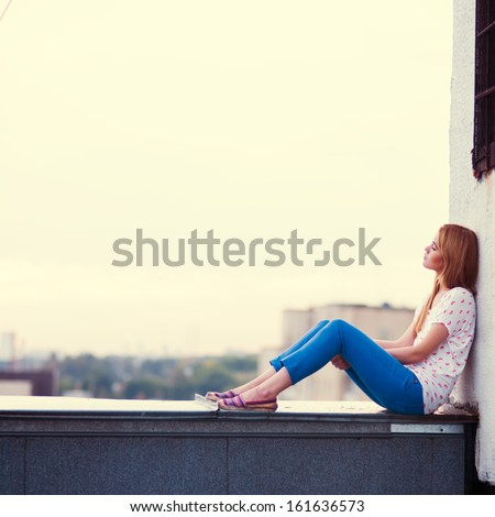 beautiful sad girl sitting on the roof of the house
