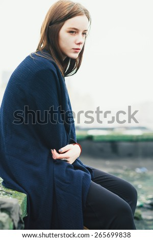 beautiful sad girl sitting on the roof of the spring