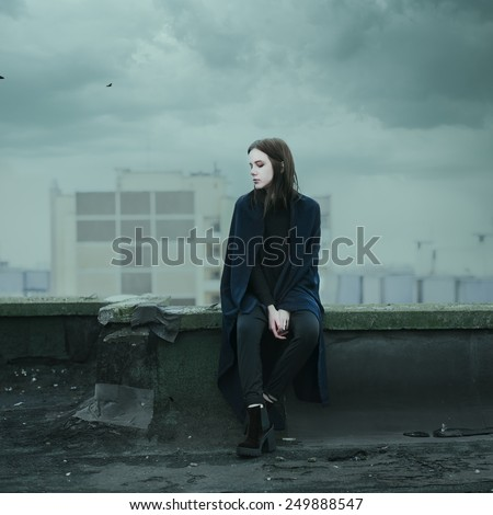 beautiful sad girl sitting on the roof on a cloudy day