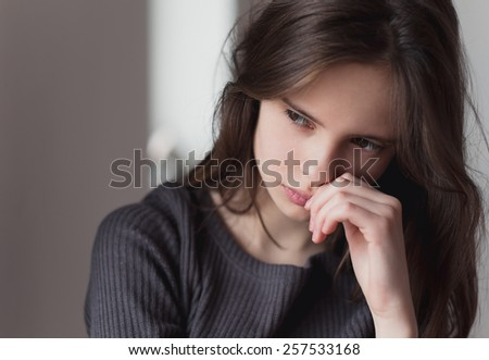 beautiful sad girl waiting at home by the window - stock photo