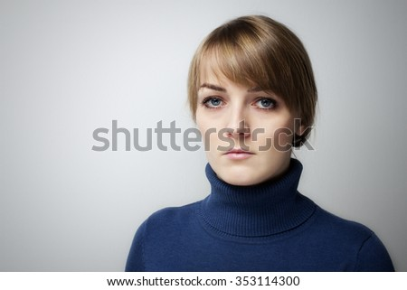 Beautiful sad girl with big blue eyes looking into the camera. Portrait of a Beautiful  girl with sad eyes on a grey background - stock photo