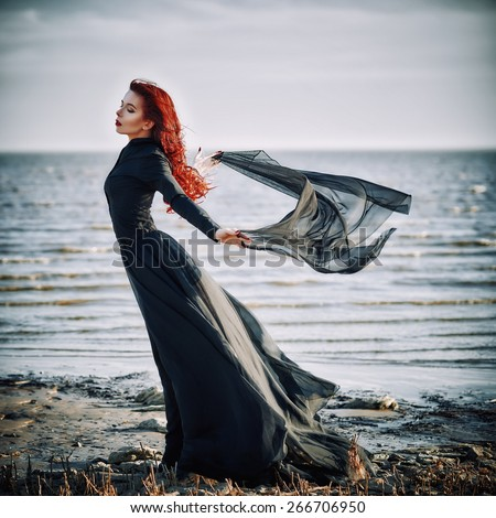 Beautiful sad goth girl with cloth in hands standing on the sea shore - stock photo