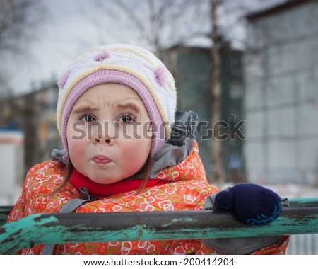 Beautiful sad kid in jacket in the winter outdoors.
