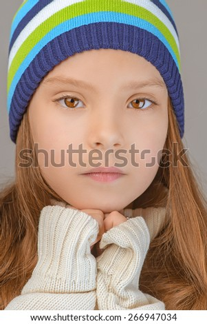 Beautiful sad little girl in knitted cap, on gray background. - stock photo