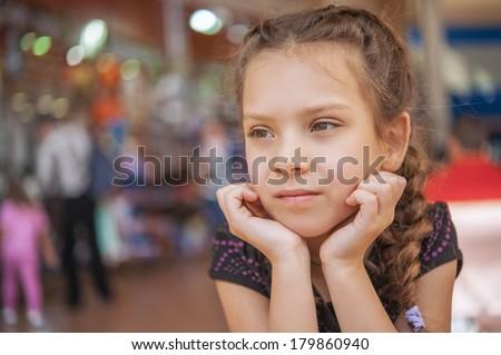 Beautiful sad little girl in market, on gray background. - stock photo