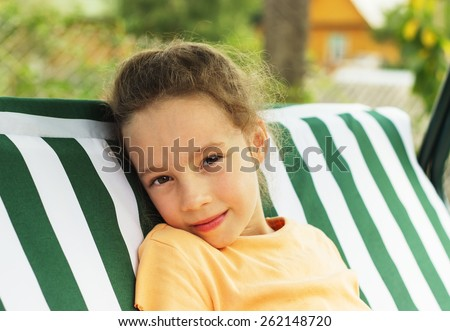 Beautiful sad school girl is resting against green of summer park. - stock photo