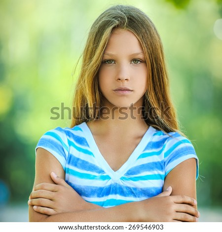 Beautiful sad teenage girl in blue blouse, against green of summer park.