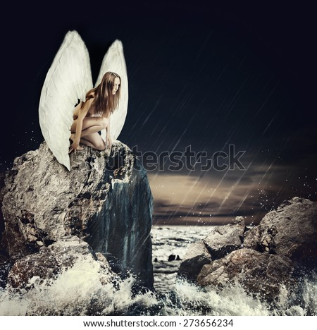 Beautiful sad woman fallen angel with white wings and long hair sitting on a rock about sea
