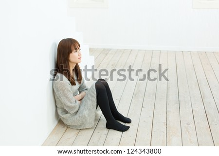 Beautiful sad woman in the room - stock photo