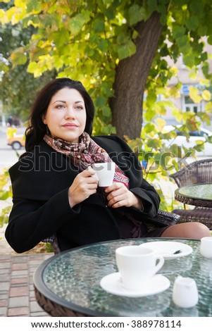 Beautiful sad woman with coffee in the autumn - stock photo