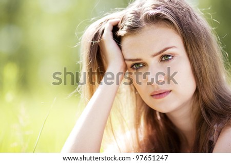 beautiful sad young woman  in the park  on a warm summer day