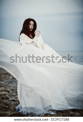 Beautiful sad young woman in white dress standing on the sea beach - stock photo