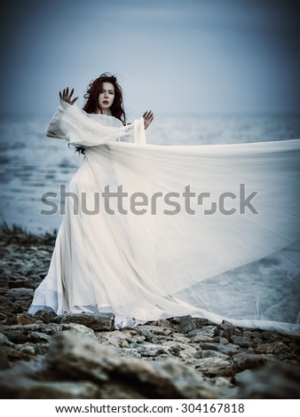 Beautiful sad young woman in white dress standing on the sea coast - stock photo