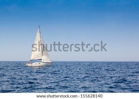 beautiful sailboat with a white sail, blue Mediterranean sea ocean horizon - stock photo