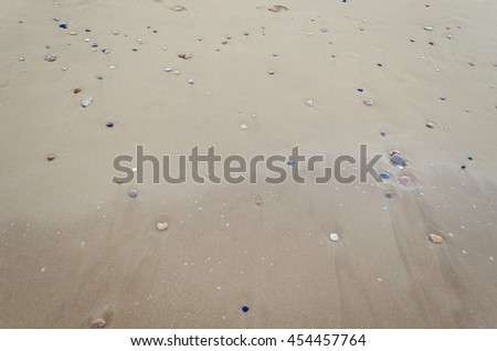 Beautiful sand background with little stones. Close up view beach sand background. Sandy texture with stones.. Brown sand. Background from fine sand. Sand background. Summer concept. Top view. - stock photo