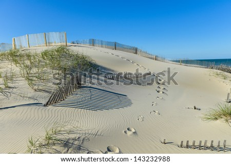 Beautiful Sand Dune with Grasses and Pretty Fence - stock photo