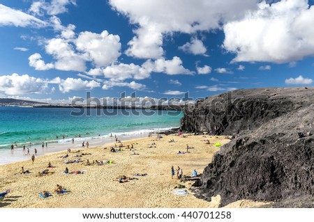 Beautiful sandy beach on the Atlantic Ocean in the village Playa Blanca / A sandy beach surrounded by volcanic mountains. Papagayo beach. Lanzarote. Canary Islands - stock photo