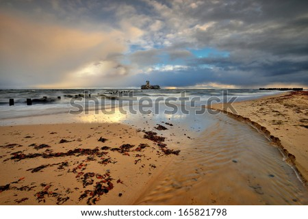 Beautiful sandy beach with a wooden breakwater - stock photo