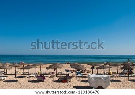 beautiful sandy beach with coconut parasols in Manta Rota (Algarve), Portugal - stock photo