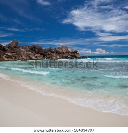 Beautiful sandy tropical beach with a rocky outcrop at the end and calm azure blue ocean under a cloudy sunny blue sky for a perfect vacation getaway