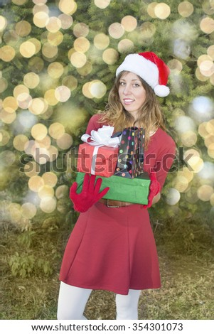 Beautiful Santa Claus girl holding Christmas presents