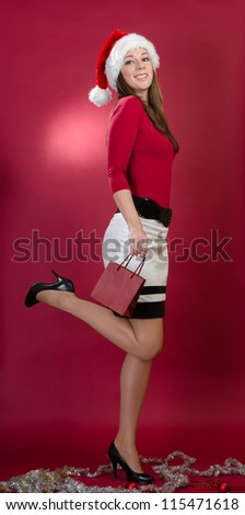 Beautiful santa woman holding a red bag and raise up leg - stock photo