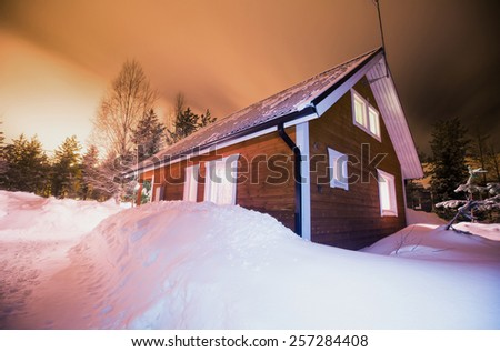 Beautiful scandinavian Finnish swedish norwegian wooden cottage cabin near slopes on a ski resort in the night time - stock photo