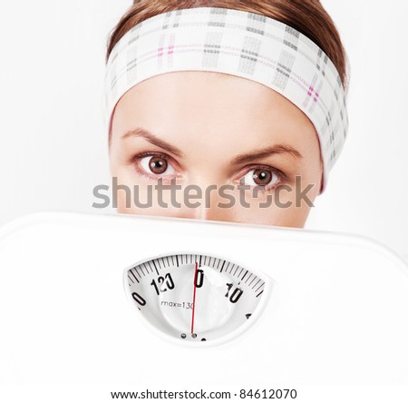 beautiful scared young blond sporty woman  holding scales - stock photo