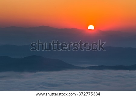 beautiful scenary in the north part of Thailand over the valley of mountain at sun rising giving a beautiful color on the mist in the field (selective focus and white balance shifting applied) - stock photo