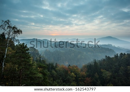 Beautiful scene of trees and mountain range against cloudy sky