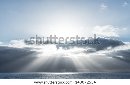 Beautiful scene with sunlight filtering through the clouds on top of the ocean - stock photo