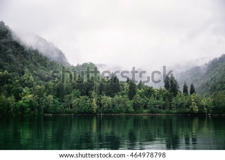 Beautiful scenery at Bled lake Slovenia. Forest, water, mountains and sky with clouds