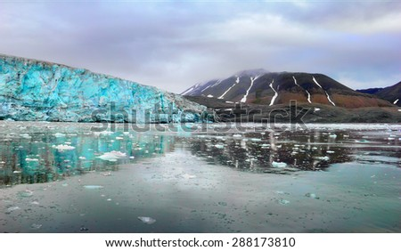 Beautiful scenery - blue ice of Esmark glacier and black mountain reflected at calm water of  Istfjorden - view from cruise ship, Spitsbergen archipelago (Svalbard island), Norway, Greenland Sea - stock photo