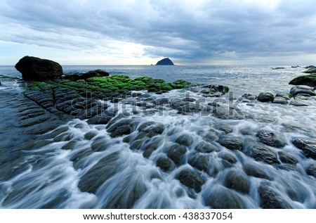 Beautiful scenery of a rocky beach in northern Taiwan on a cloudy morning, with peculiar rock formations on the coast & an island on the distant horizon under dramatic dawning sky ( long exposure ) - stock photo