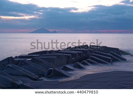 Beautiful scenery of a rocky beach in northern Taiwan on a foggy cloudy morning with a breakwater ( wave breaker ) in foreground & Guishan (Turtle) Island on distant horizon under dramatic dawning sky - stock photo