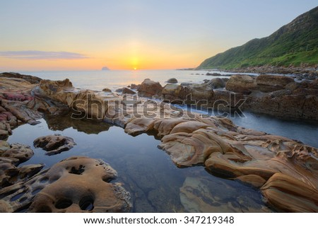 Beautiful scenery of dawning sky by rocky beach in northern Taiwan with reflection of golden sun light on tranquil sea water ~ Romantic view of sunrise by sea shore (long exposure effect)  - stock photo