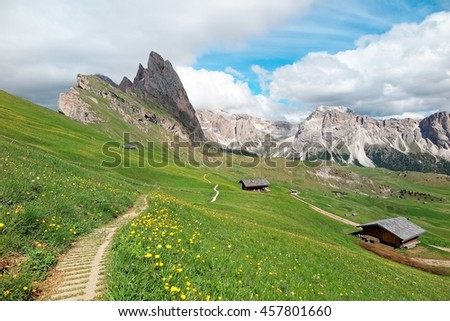 Beautiful scenery of Dolomiti on a sunny summer day with view of hiking trails on grassy hills & majestic Odle (Geisler) mountain peaks in background at Seceda, Val Gardena, South Tyrol, Italy Europe - stock photo