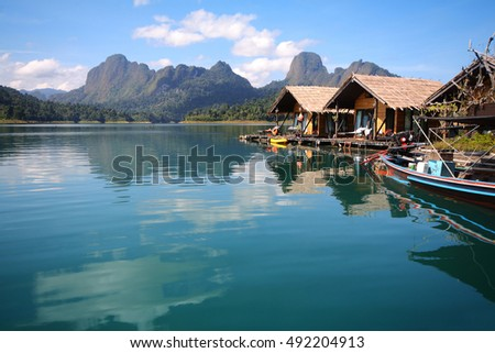 Beautiful scenery of houseboat and the beautiful water reflection with clear sky at lake river in natural attractions,Ratchaprapha Dam at Khao Sok National Park,Surat Thani Province in Thailand.
