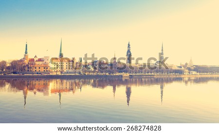 Beautiful scenery of Riga center with reflection in Daugava, with retro filter effect - stock photo