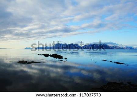 Beautiful scenic landscape - dramatic cloudy sky reflected at calm blue water against the background of distant rugged mountain range, Spitsbergen archipelago (Svalbard island, Norway), Greenland Sea - stock photo