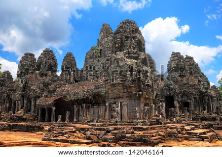 Beautiful scenic landscape with ancient Bayon temple (UNESCO world heritage site) - wide angle view - against the background of dramatic cloudy blue sky near Siem Reap, Cambodia, South East Asia - stock photo