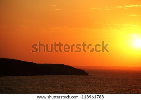 Beautiful scenic landscape with going down sun and dramatic colorful sky at sunset time and silhouette of black cape at foreground in Taman, Krasnodar Krai, Azov sea, Russia, august - 2012 - stock photo