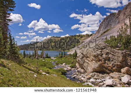 Beautiful scenic photograph of the high mountains of Wyoming at the peak of summer with billowy clouds, green vegetation and melting snow. - stock photo